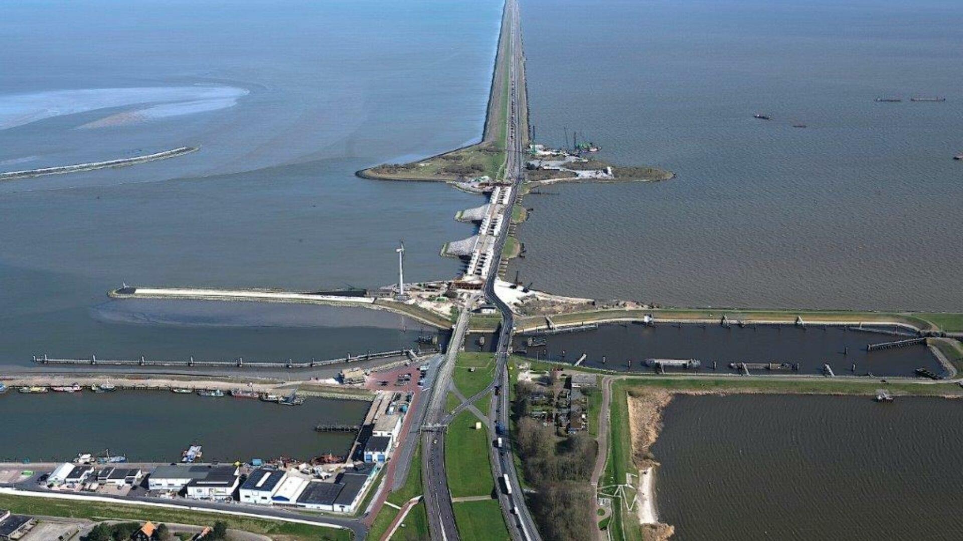 Luchtfoto van de Afsluitdijk. Je kijkt van boven, van de kant bij Den Oever, uit op de sluizen. Uit beeld loopt de lange Afsluitdijk naar achter. Aan weerskanten het water van het IJsselmeer en de Waddenzee.