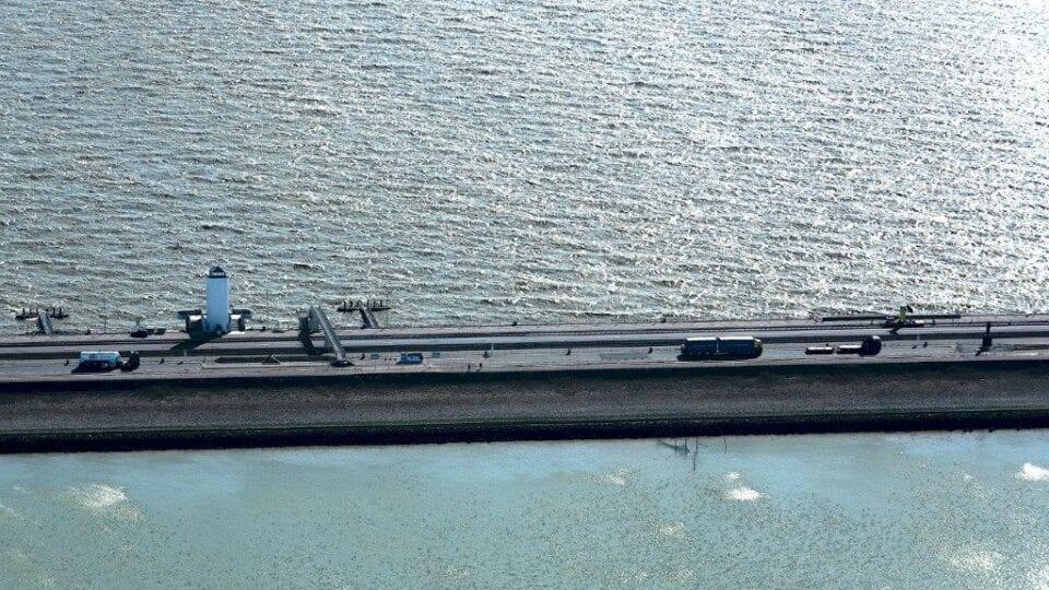 Luchtfoto van de Afsluitdijk. Je kijkt van boven op de weg tussen Zurich en Den Oever. Aan de zijkanten van de weg zie je water. Je kan zien dat de foto genomen is bij het monument. Dit komt omdat je de witte uitkijktoren van het Vlietermonument ziet. monument