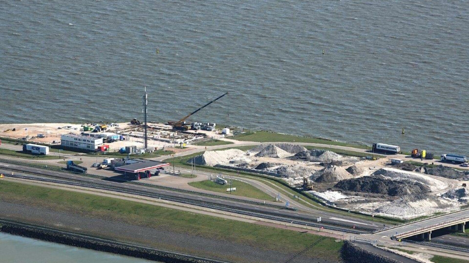 Luchtfoto van de Afsluitdijk. Je ziet een klein stukje met een bouwterrein. Er staan een paar vrachtwagens, hefkraan en klein gebouwtje. Verder kijk je vanuit het IJsselmeer en zie je een stuk van de Waddenzee. Ook zie je een deel met zandhopen.