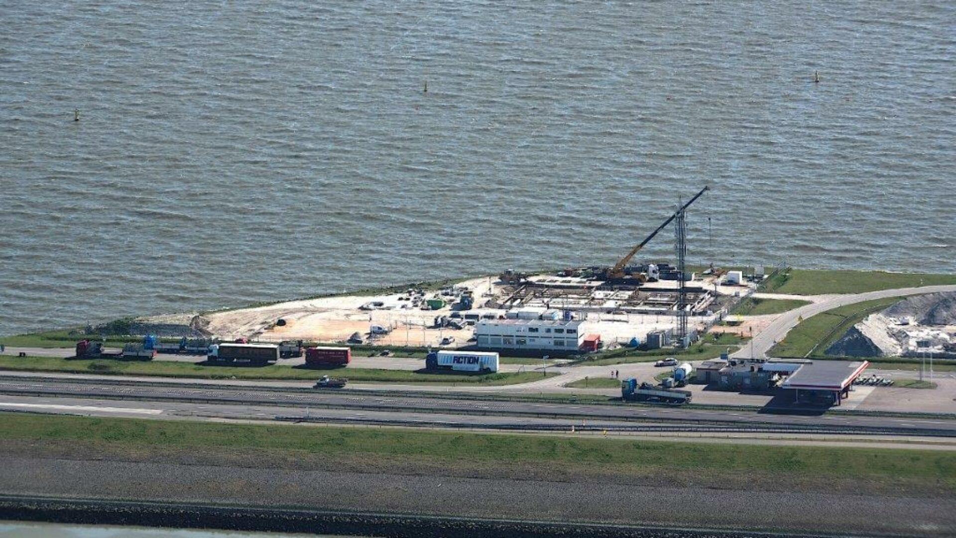 Luchtfoto van de Afsluitdijk. Je ziet een klein stukje met een bouwterrein. Er staan een paar vrachtwagens, hefkraan en klein gebouwtje. Verder kijk je vanuit het IJsselmeer en zie je een stuk van de Waddenzee.