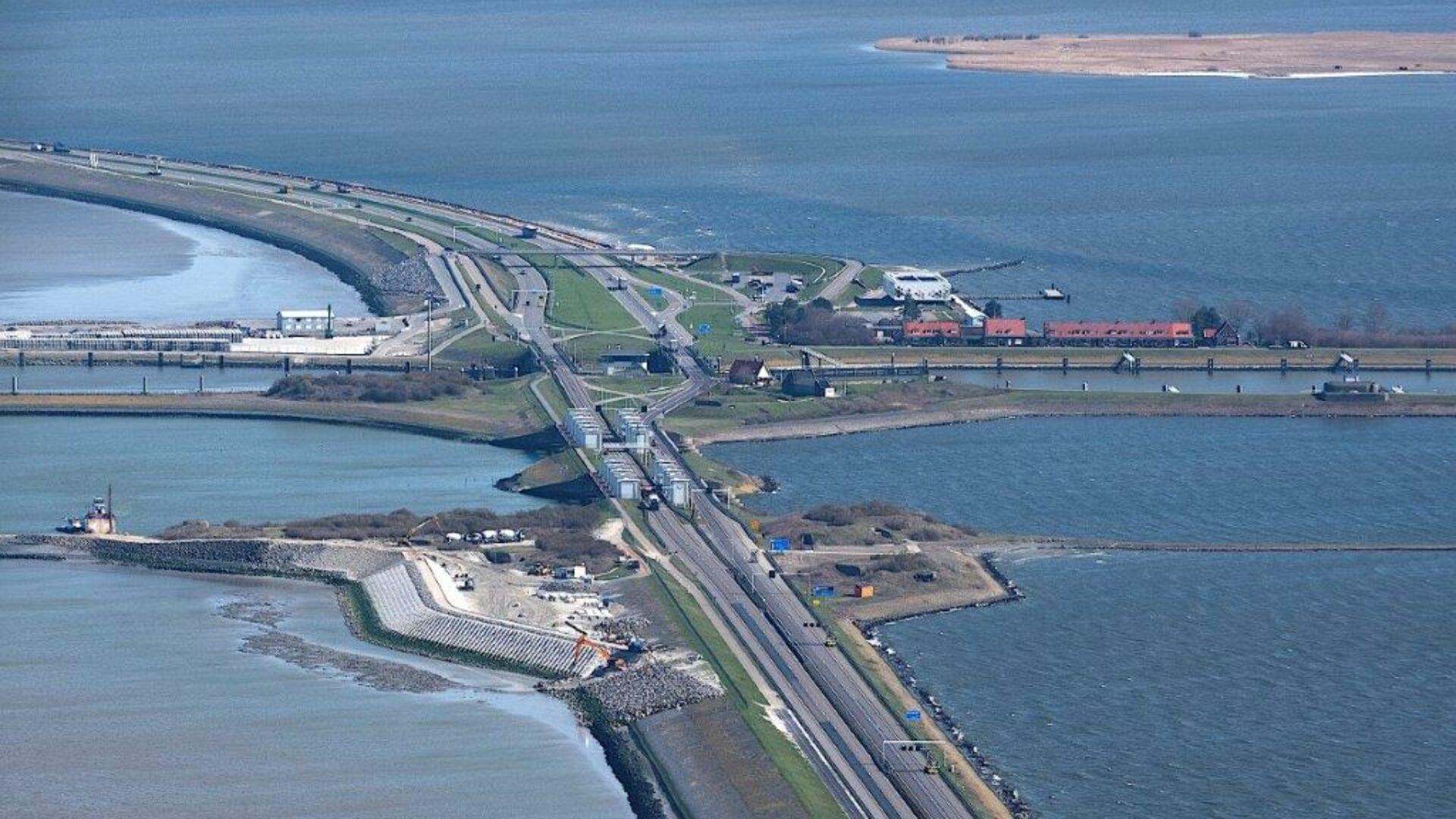 Luchtfoto van de Afsluitdijk. Je ziet van boven op Kornwerderzand. Je kijkt vanuit de kant van Den Oever. Je ziet de weg tussen de twee wateren en aan de zijkant een paar huisjes van Kornwerderzand. Daarachter het Afsluitdijk Wadden Center. De weg loopt dan met een bocht links uit beeld. Rechts in het IJsselmeer zie je een zandbank.