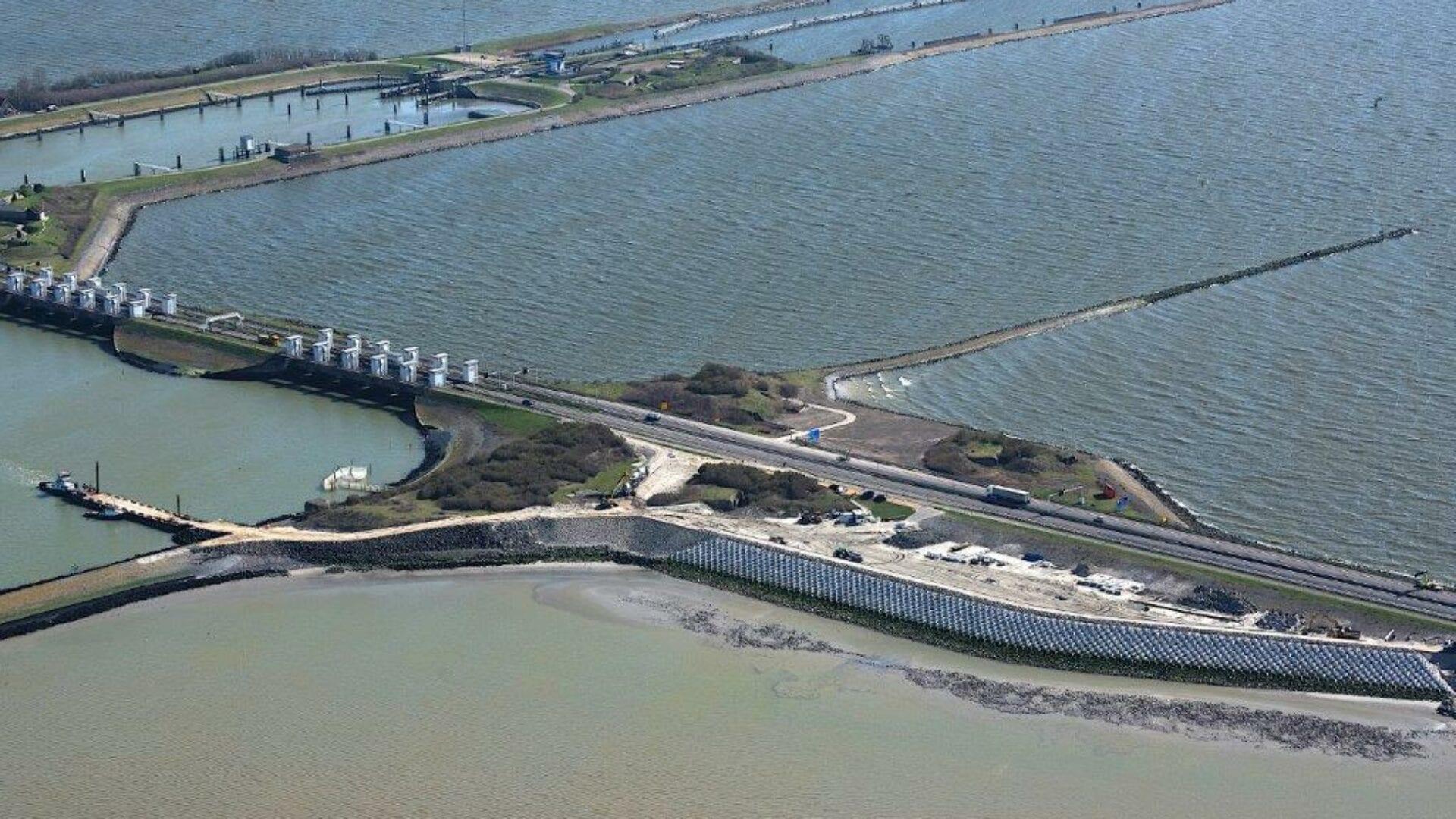 Luchtfoto van boven met in beeld de Afsluitdijk. Op de foto zie je de sluizen van Kornwerderzand. Aan de zijkanten zie je het water van het IJsselmeer en de Waddenzee. De weg aan de kant van de Waddenzee heeft een speciale wand met blokken.
