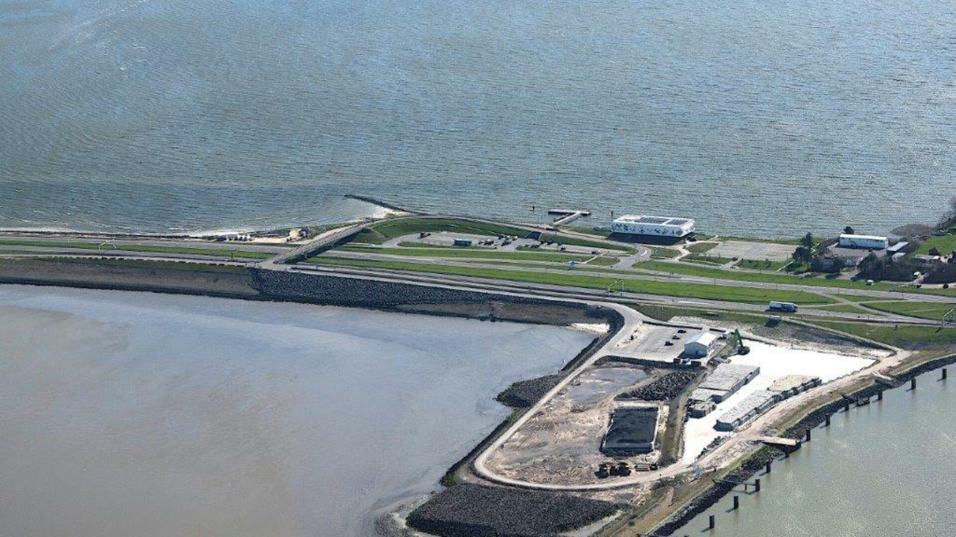 Luchtfoto van de Afsluitdijk. Deze is van boven genomen bij Kornwerderzand, specifiek DNA. In beeld zie je een bouwterrein van het werkeiland, een museum (Het Afsluitdijk Wadden Center) en het kantoor van De Nieuwe Afsluitdijk.