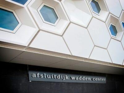 Wij kijken op de voorgevel van het Afsluitdijk Wadden Center. Deze bestaat uit een aantal witte zeshoekige blokken en ramen. Onder de gevel hangt een bordje met de naam van het museum.