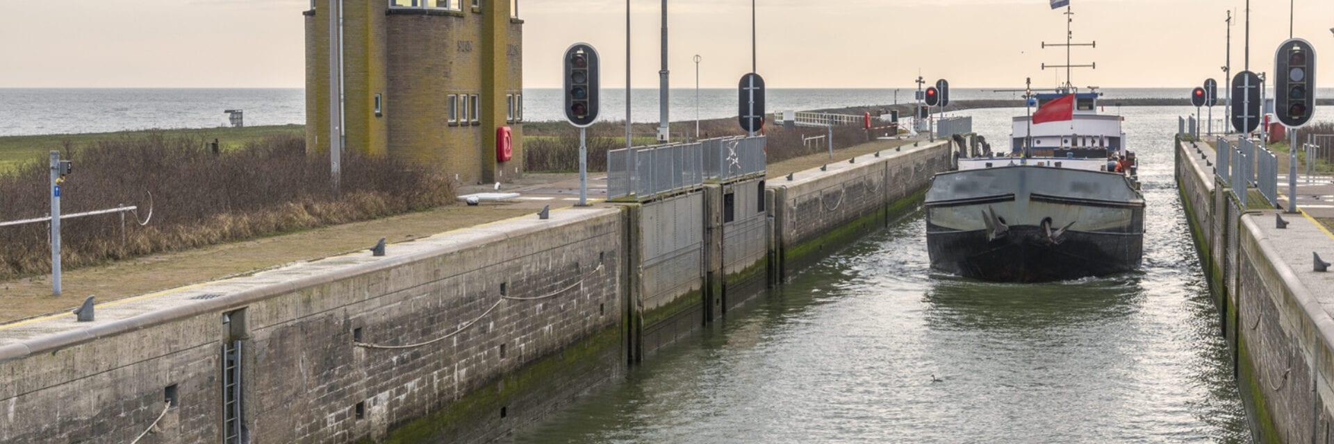 Wij kijken vanaf de kant op de sluizen. In de sluis vaart een witte boot en aan de rechterkant, op de kade, zie je een gebouwtje. Aan het einde zie je het water van het IJsselmeer.
