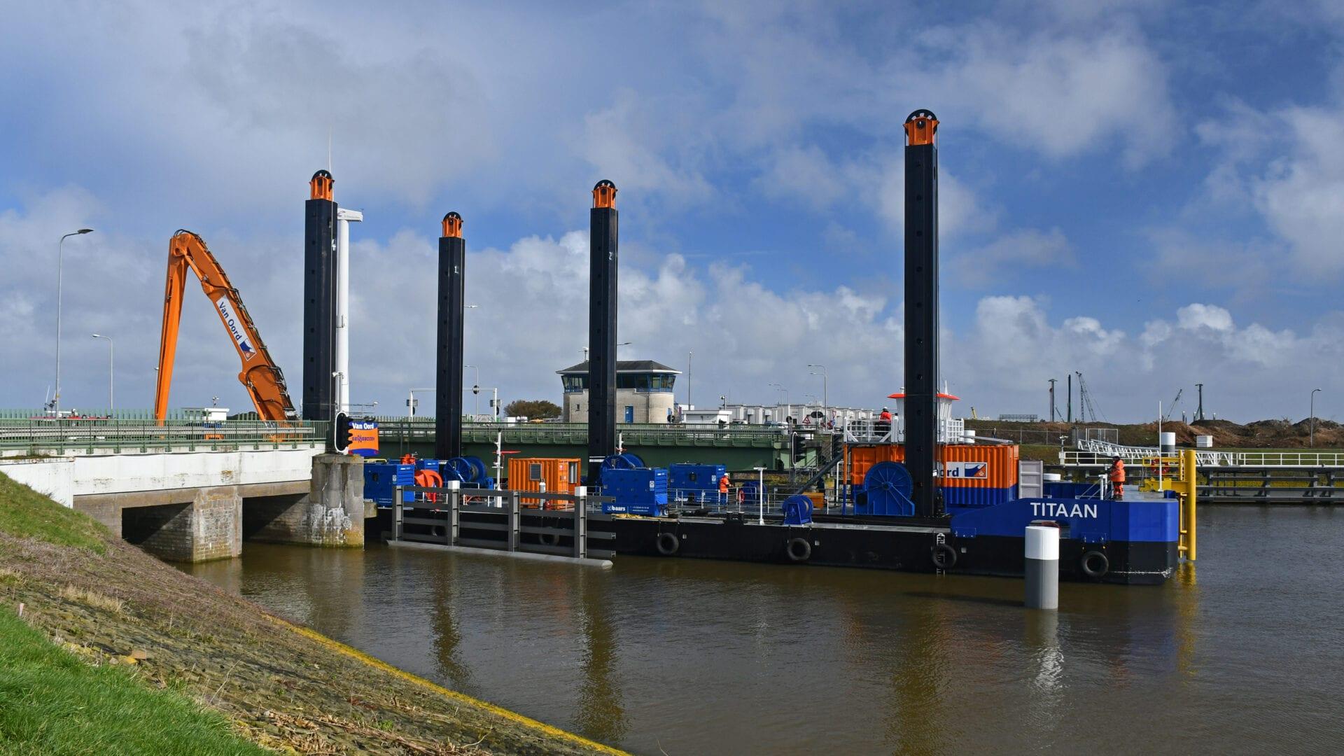 Wij kijken over het water bij de Afsluitdijk. Op de achtergrond zie je een grote boot met een aantal zwarte palen varen. Hij brengt Levvel-blocs van de Waddenzeekant met een schip naar de andere kant. Aan de achterkant van het schip staat een oranje graafmachine.