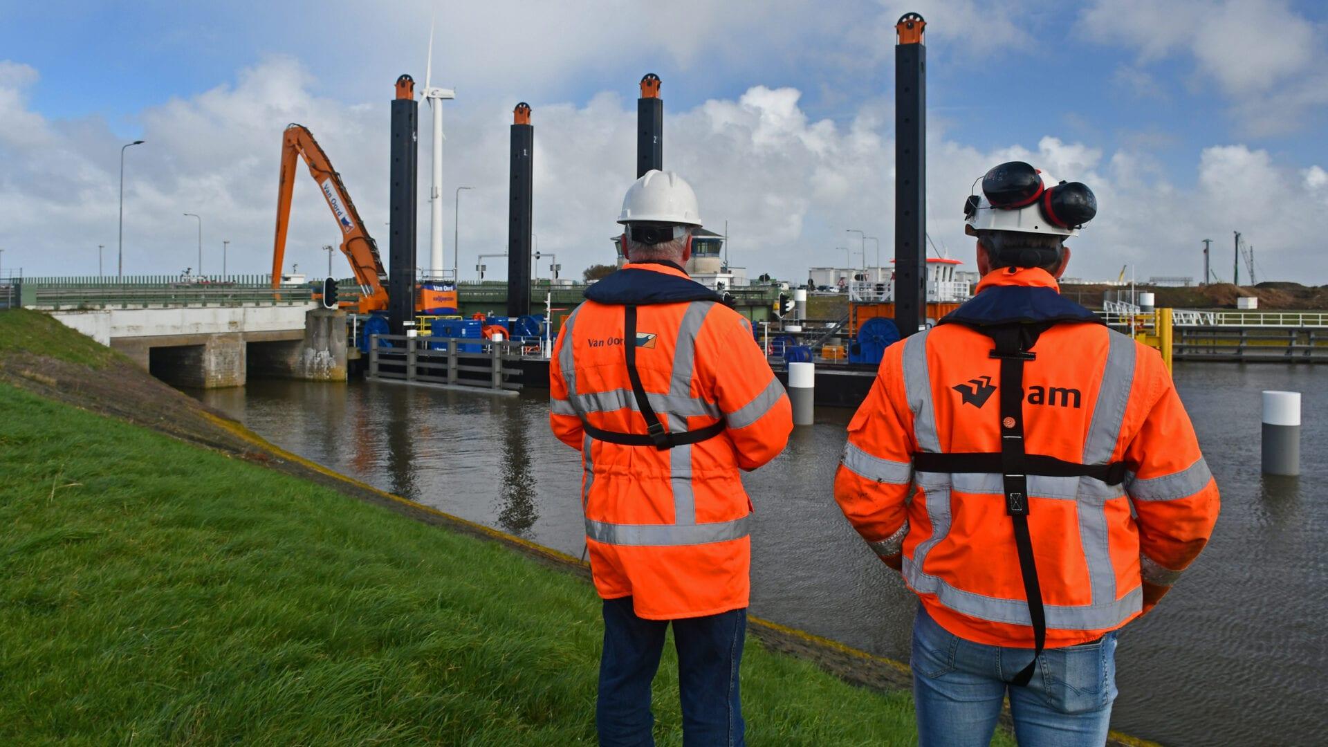Wij kijken uit op de rug van twee mannen in oranje veiligheidsjassen. Op de ene jas zie je duidelijk het logo van BAM staan. Zij staan uit te kijken over het water bij de Afsluitdijk. Op de achtergrond zie je een grote boot met een aantal palen varen. Hij brengt Levvel blocs van de Waddenzeekant met een schip.