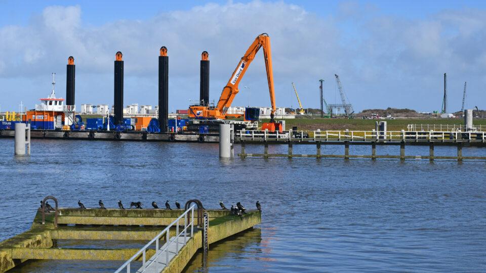 Deze foto toont het water en een steiger met vogels. Verderop zie je de aankomst van de Titaan. Dit is een blauwe boot met zwarte palen. Op de boot zie je een oranje graafkraan.