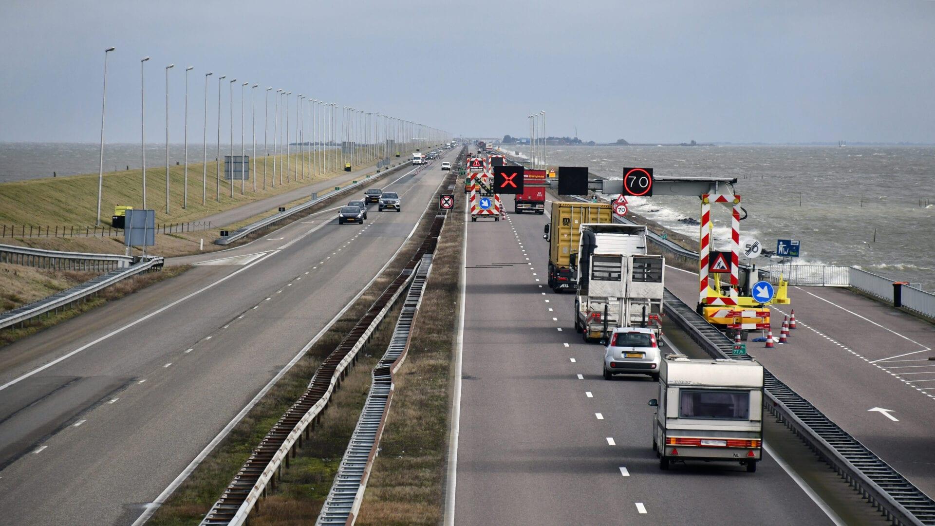 Wij kijken op de weg bij de Afsluitdijk. Je ziet 5 wegbanen. Rechts rijden er veel auto's. Dit komt omdat 1 weghelft gesloten is. Daarom hangt er een kruis boven weg en aan de zijkant een 70km bord.