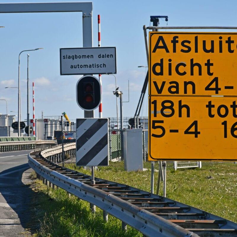 Op de foto zie je het begin van de Afsluitdijk. Aan de weg zie je een verdrijvingsvlak. Aan de zijkant zie je een sluisgebouw en een slagboom. Aan de zijkant zie je een wit bord met de tekst: Slagbomen dalen automatisch. Voorin staat een geel bord over de afsluiting: Afsluitdijk dicht van 4-4 18uur tot 5-4 16uur