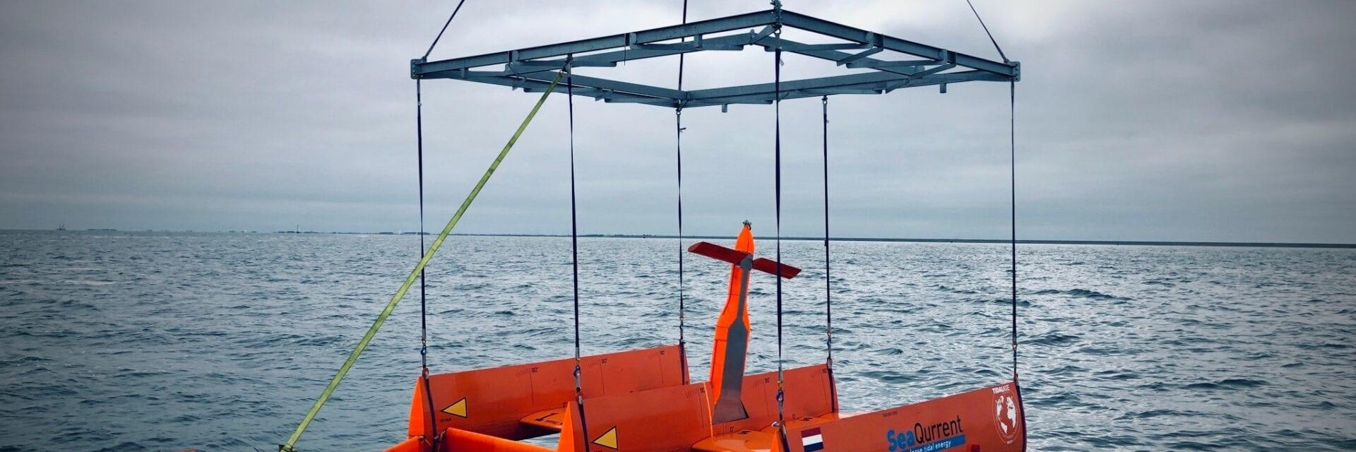 Je ziet een foto van de Waddenzee. De foto is te hoogte van het water genomen. Net daar boven zie je een oranje stellage. Dit is een soort vlieger met drie turbines en een propeller. Aan een aantal draden wordt de stellage het water ingezakt.