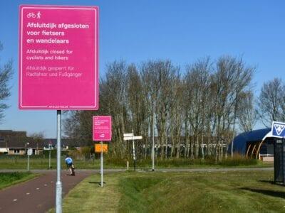 Je ziet een groene omgeving met bomen en een fietspad. Er staan twee roze fietsborden op de foto. Op het voorste bord kun je een tekst lezen: Afsluitdijk afgesloten voor fietsers en wandelaars. Afsluitdijk closed for cyclists and hikers. Afsluitdijk gesperrt für Radfahrer und Fußgänger.