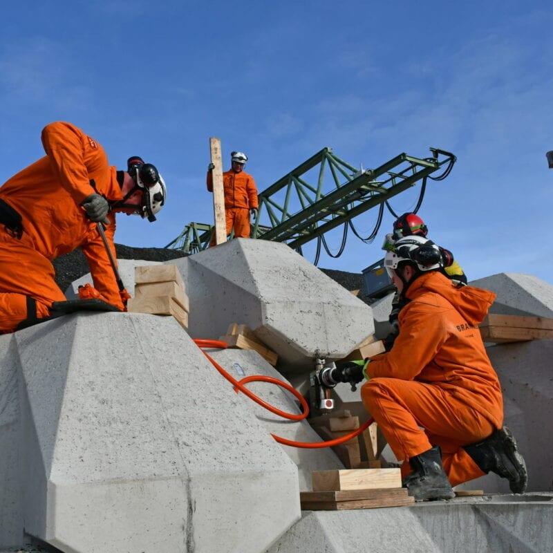 Veiligheidsoefening met Levvelblocs. Je ziet drie personen in oranje pakken knielen bij de blokken. Deze blokken zijn in een hoekige vorm gemaakt. Zij plaatsen een hefboom-systeem tussen de blokken. En liften de blokken zo omhoog. Boven de blokken zie je de lucht en een hijskraan.