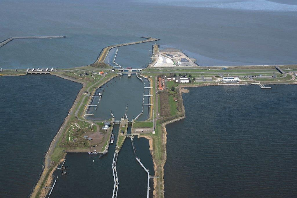Dit is een luchtfoto van de nieuwe sluis vij Kornwerderzand. Aan de linkerkant zie je water, dit zie je ook aan de rechterkant. In het midden zit een sluisdoorgang.