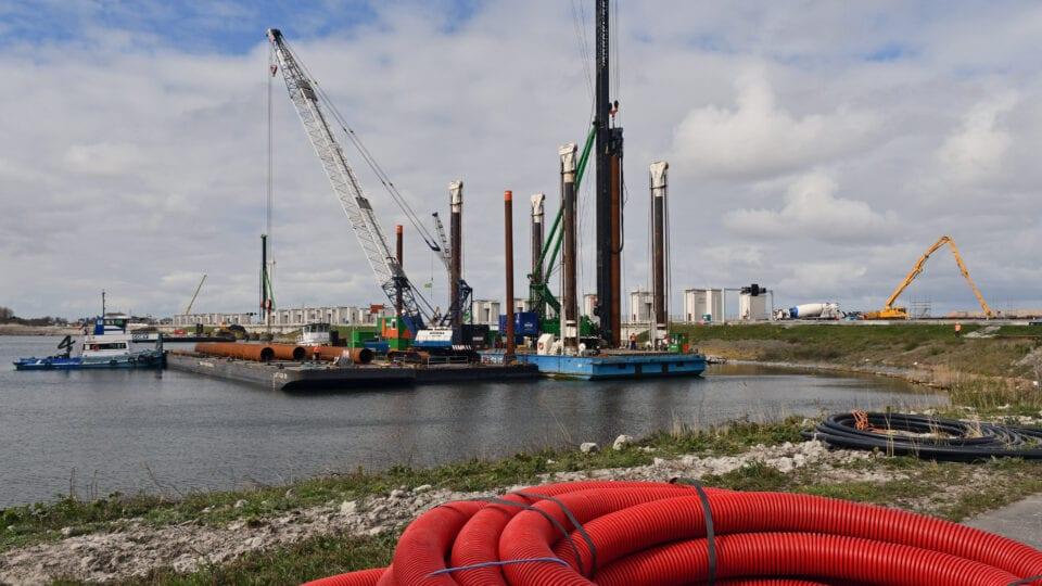 De buispalen en damwanden voor het tweede pompgemaal bij Den Oever worden met een ponton geplaatst. We kijken uit over het water bij de Afsluitdijk. In het midden zie je een grote, drijvende machine.