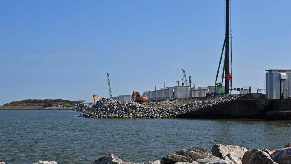 Bij de nieuwe spuisluizen van Den Oever worden heiplateaus aangebracht door oranje kranen. We kijken hier uit over het water bij de Afsluitdijk.