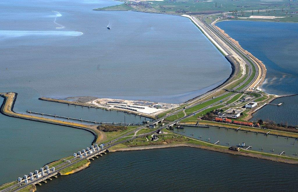 Op de foto zie je de nieuwe sluits van Kornwerderzand. De foto is van bovengenomen. Door het beeld loop de weg van de Afsluitdijk. Aan beide kanten van de Afsluitdijk zie je groen en water.