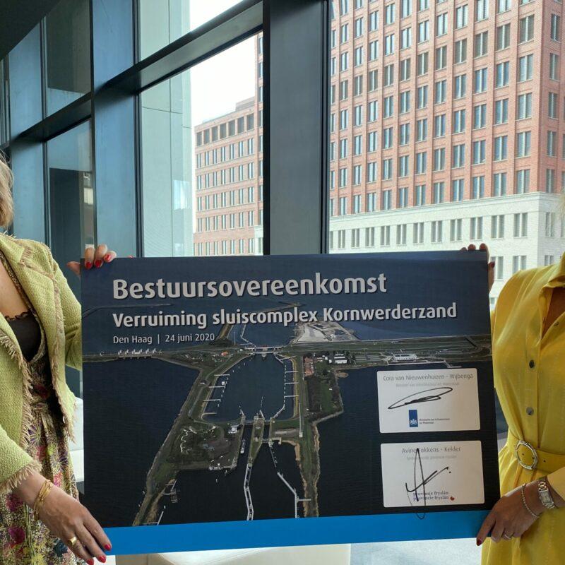Op de foto zie je de gedeputeerde (Avine Fokkens) en de minister staan. Zij houden samen een grote cheque omhoog. Op de cheque zie je een afbeelding van de sluis.