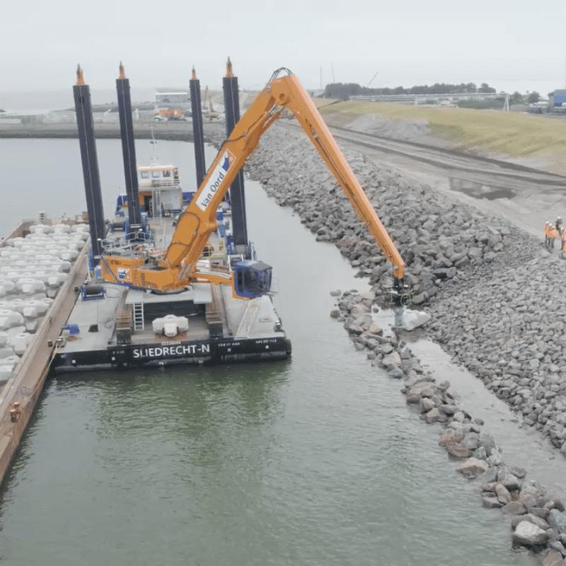Een kraan op een ponton haalt Levvel-blocs uit een vrachtboot en plaatst die op de dijk.