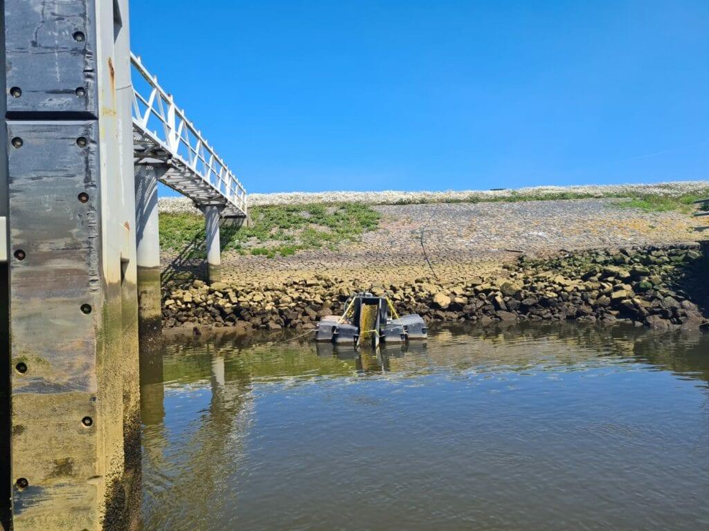 Wij zien het water van de Afsluitdijk. Aan de achterkant zie je een stuk dijk. In het water, voor de dijk, ligt een detectieboot. Links zien we een steiger.
