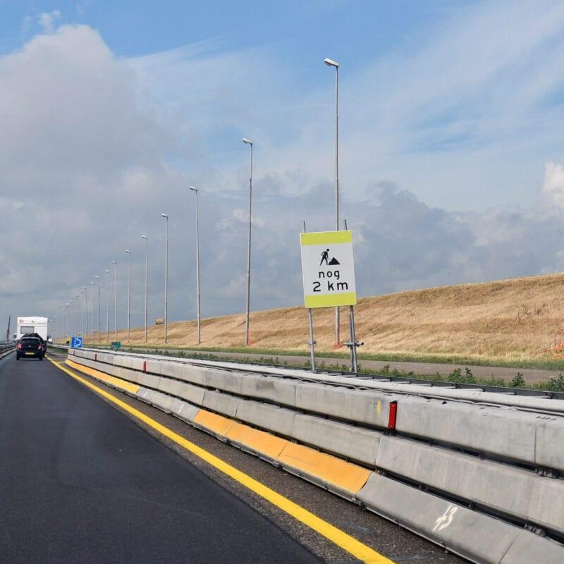 Je ziet een weg die versmald is met behulp van een metalen railing en een gele doorgetrokken streep. Aan de rechterkant van de weg staat een bord met de tekst nog 2 kilometer.