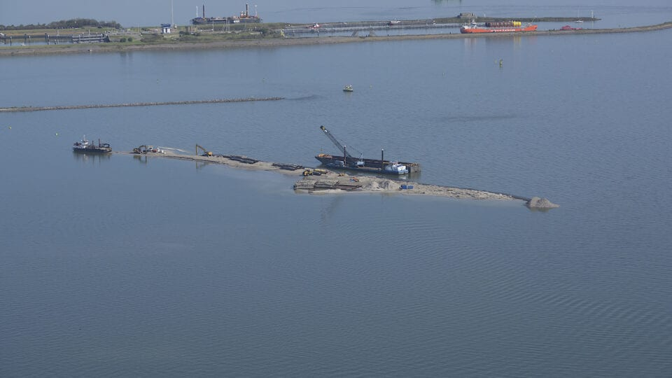 Op de foto zie je een werkeiland dat later een natuureiland wordt. Je ziet een landstrook met een boot.