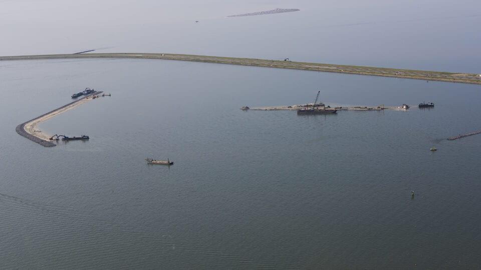 Op de afbeelding zie je de luwtedam. Dit is een gebogen landstrook omringt door water. In het water liggen drie boten.