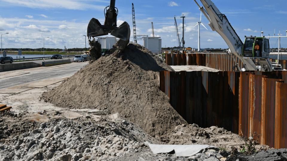 Nadat aan de kant van de Waddenzee de damwanden en buispalen zijn aangebracht wordt de bouwkuip met zand aangevuld en ontstaat de zogenaamde kofferdam. Vanaf hier worden de nieuwe spuigroepen gebouwd.