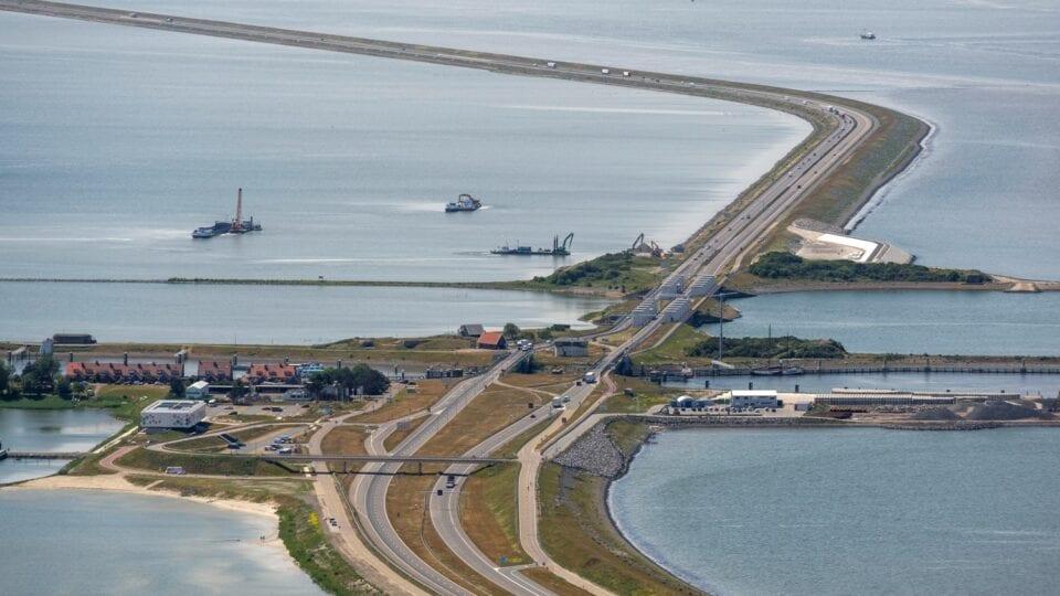 Op de foto zie je een de Afsluitdijk. Links zie je de huizen van Kornwerderzand en het museum. Verder is de dijk omringt met water.