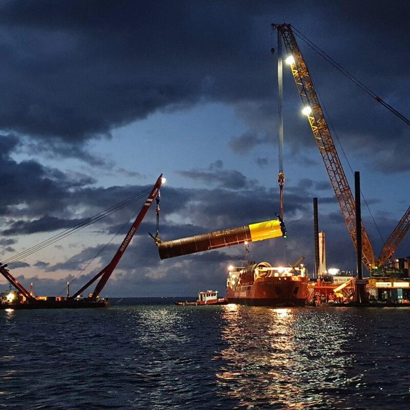 Op de foto zie je twee boten die een paal uit het water tillen. Het is bijna donker en op de boten staan lampen.