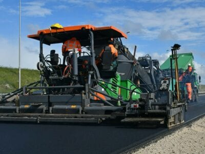 Op de foto zie je een grote asfalteermachine aan het werk. Over de volle breedte van de rijbaan maakt de machine het asfalt glad. Een werkman in oranje werkkleding staat links van de weg en controleert het asfalt.