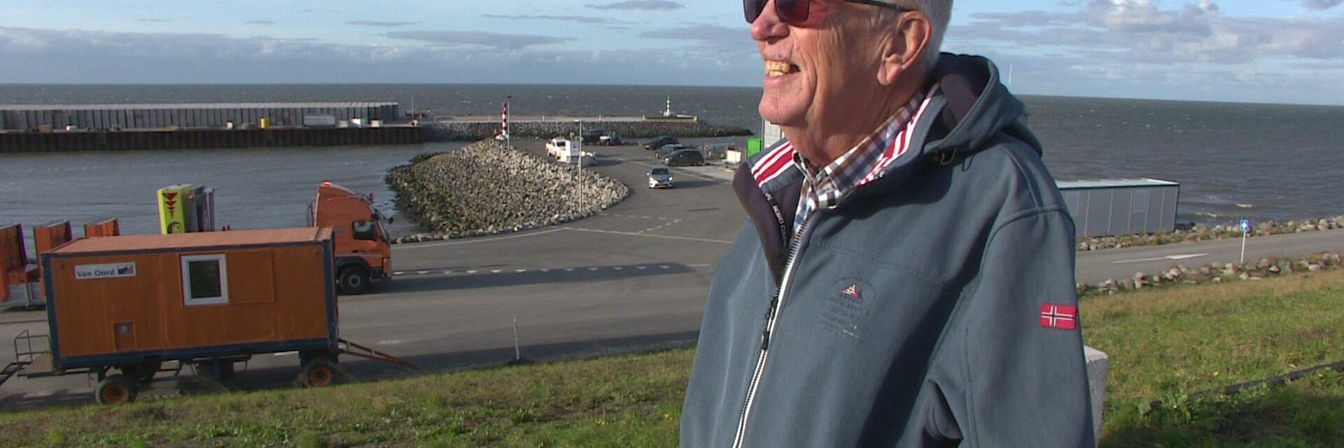 Op deze foto zie je Jan de Krijger, hij is een vrijwilliger en kijkt uit over de dijk. Hij draagt een zonnebril.