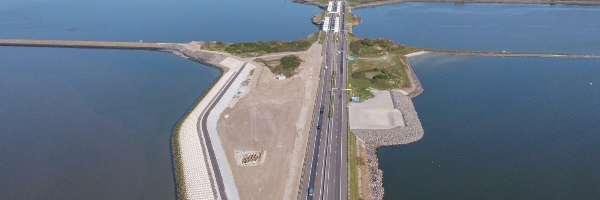 Je ziet een luchtfoto van de Afsluitdijk. Der weg loopt recht naar boven met aan het einde een bocht naar links. De Afsluitdijk wordt omringt door water.