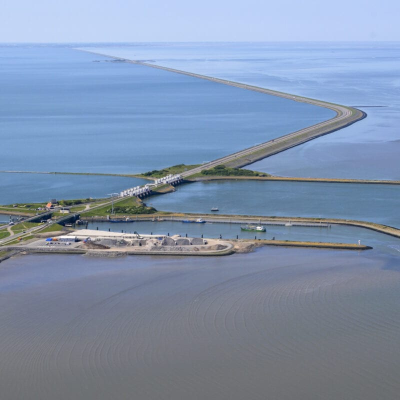 Op de foto zie je de nieuwe sluis van Kornwerderzand. De foto is van bovengenomen. Door het beeld loop de weg van de Afsluitdijk. Aan beide kanten van de Afsluitdijk zie je groen en water.