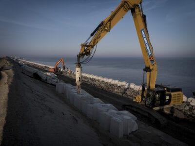 De dijk wordt versterkt door middel van het plaatsen van blocs door een kraan.