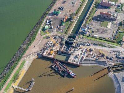 Je ziet hier de keersluis bij Den Oever, bij de Stevinsluizen. De foto is vanuit de lucht genomen en biedt overzicht van het werkgebied en de bouwkuip.