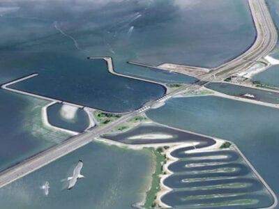 Impressie van de Vismigratierivier. Je ziet een getekende versie van de Afsluitdijk. In de Afsluitdijk is de Vismigratierivier getekend. Dit is een slingerende rivier, omlijnd met grondstroken. Aan de kant van de Waddenzee zie je een uitmondingshaven.