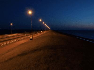 Op deze afbeelding zie je de Afsluitdijk bij nacht met aangepaste lantaarnpalen die diervriendelijker zijn.