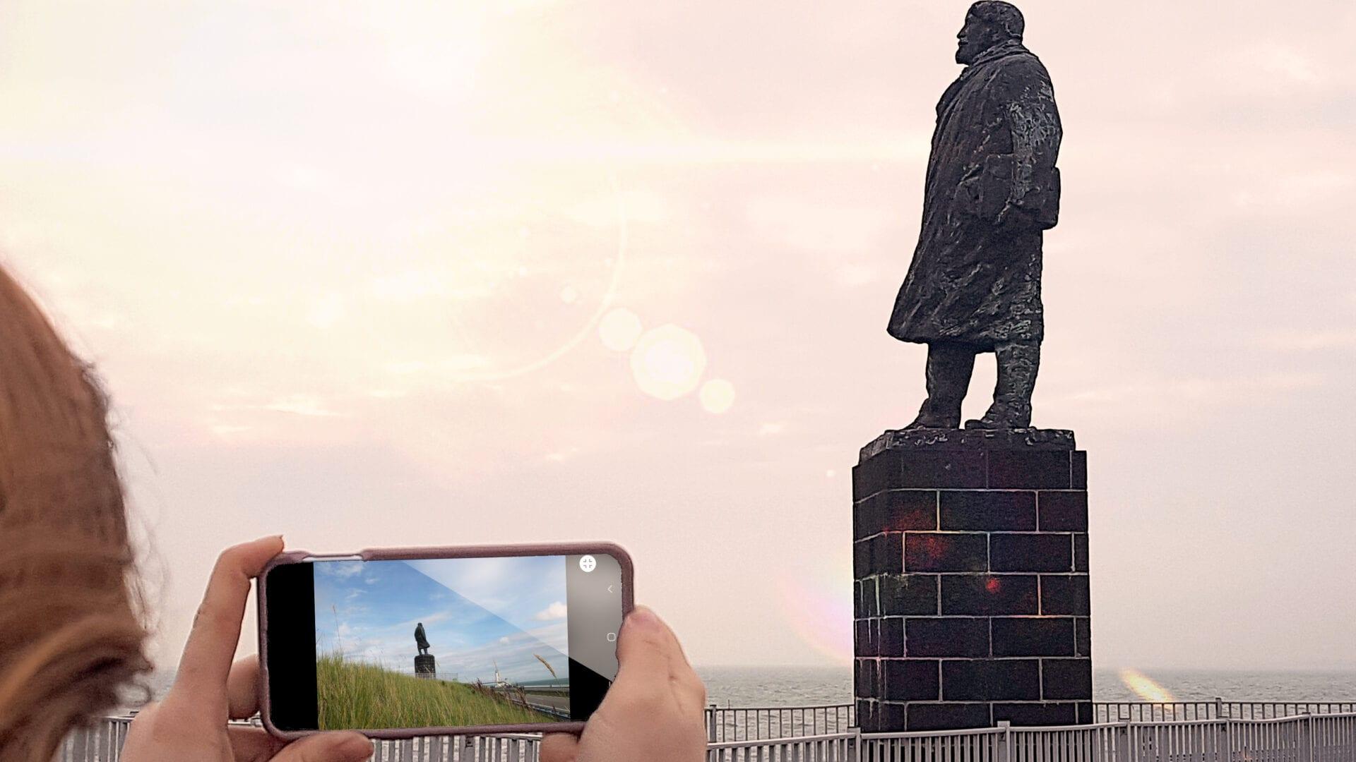 Op deze foto zie je een vrouw een telefoon vasthouden, ze staat voor het standbeeld van Lely.