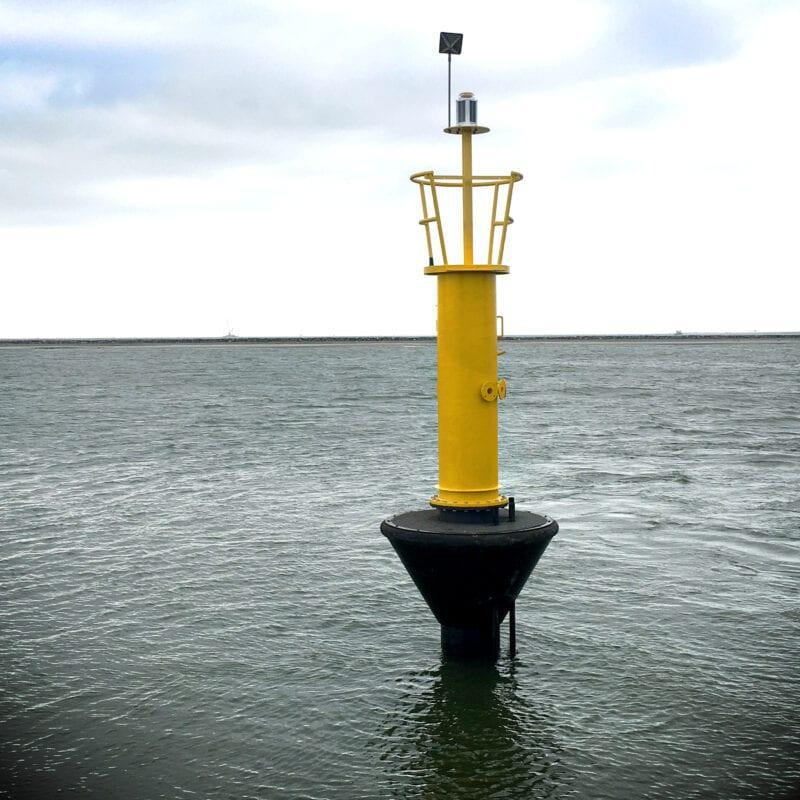 zouwatermeter in het ijsselmeer, dit is een gele paal die op een zwarte boei staat midden in het water.