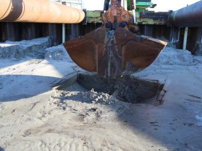 De allereerste hap grond uit de Afsluitdijk voor de coupure van de Vismigratierivier