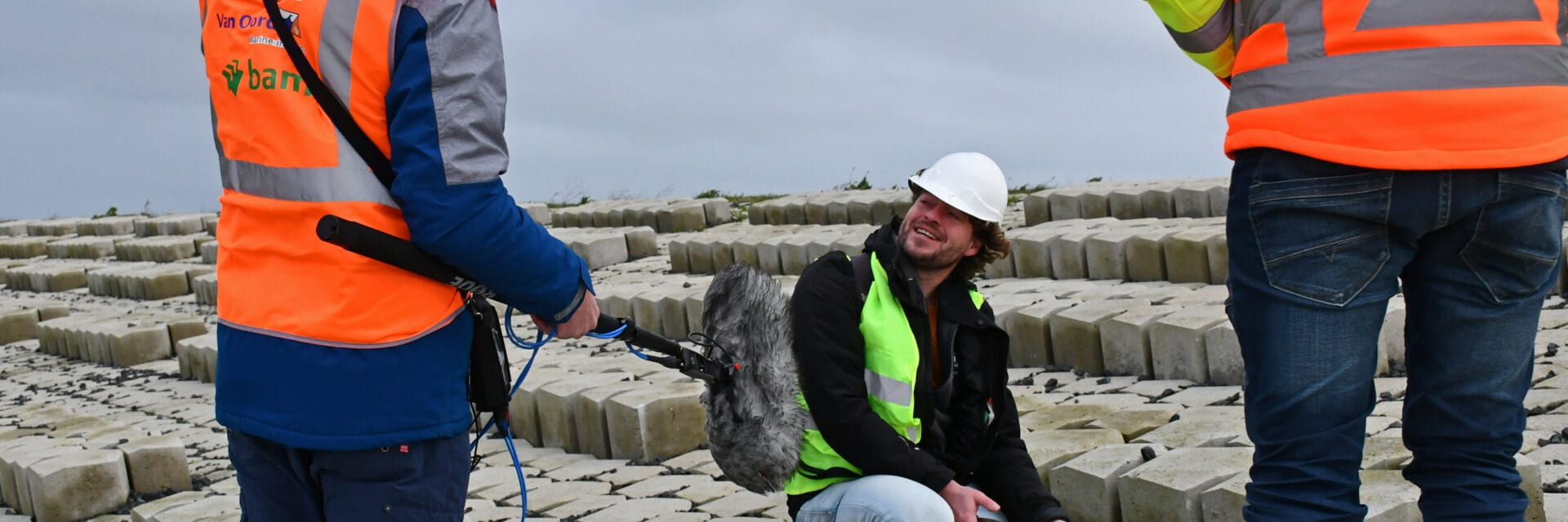 iemand zit met een plantenspuit bij een zaadbolletje van de wilde kool op de Afsluitdijk en wordt daarover geïnterviewd voor Vroege Vogels