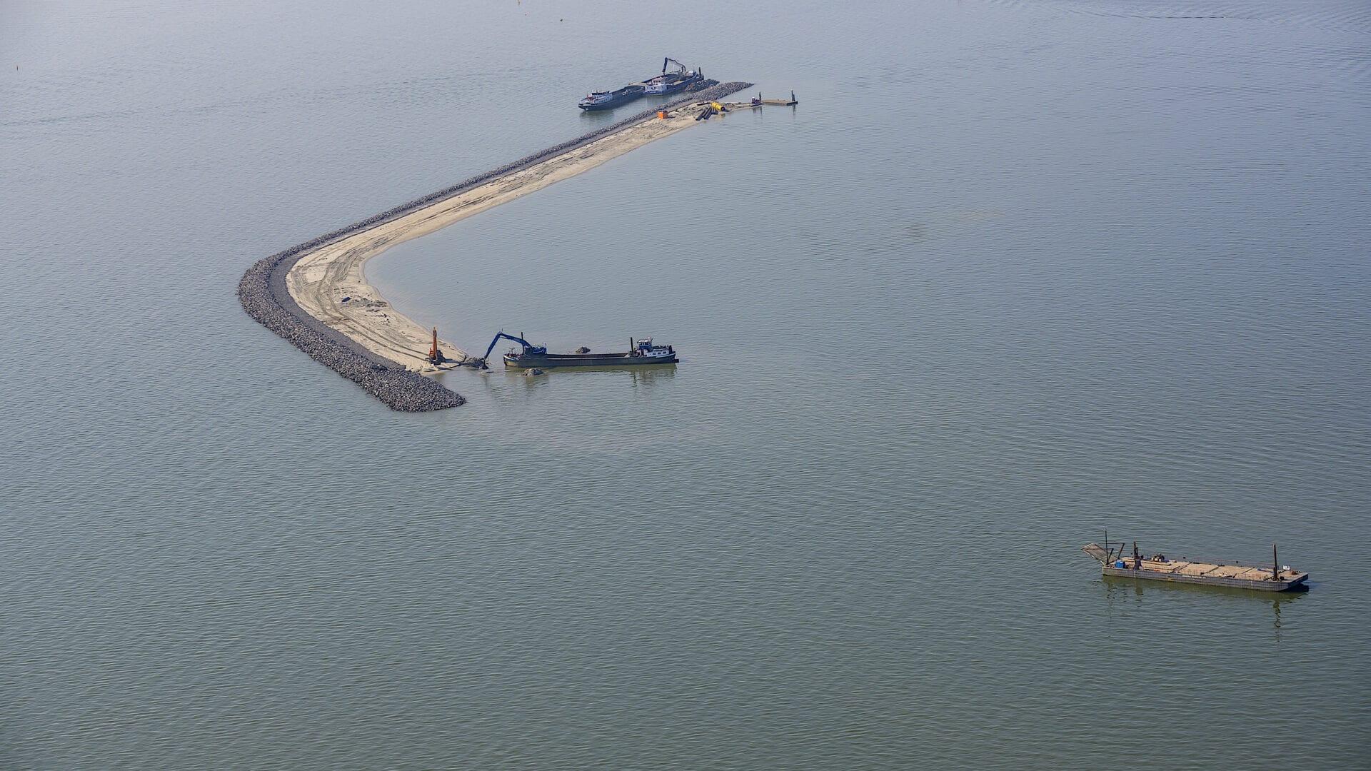 Op de afbeelding zien we twee boten die werken aan een dam in het water.