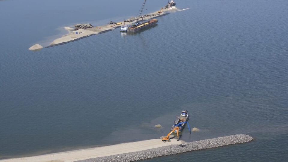 Op de afbeelding zien we twee boten die werken aan een dam in het water. Op de voorgrond zie je een andere boot.