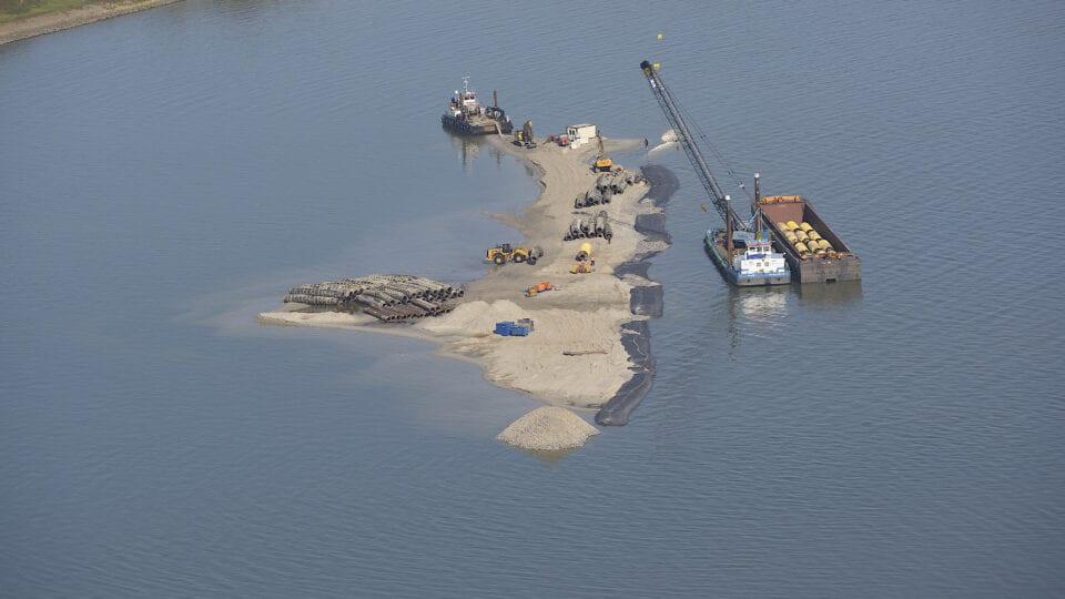 Op de afbeelding zie je een boot werken aan een strookje land in het water bij de Afsluitdijk.