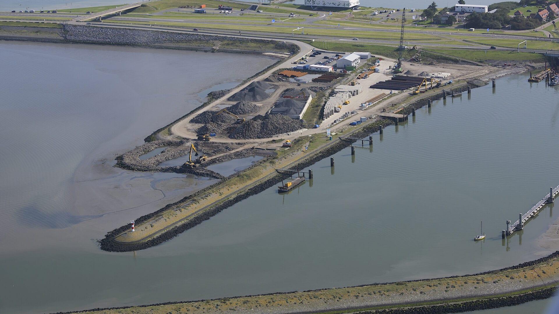 Dit is een luchtfoto van de Afsluitdijk. Je kijkt van boven op een werkterrein.