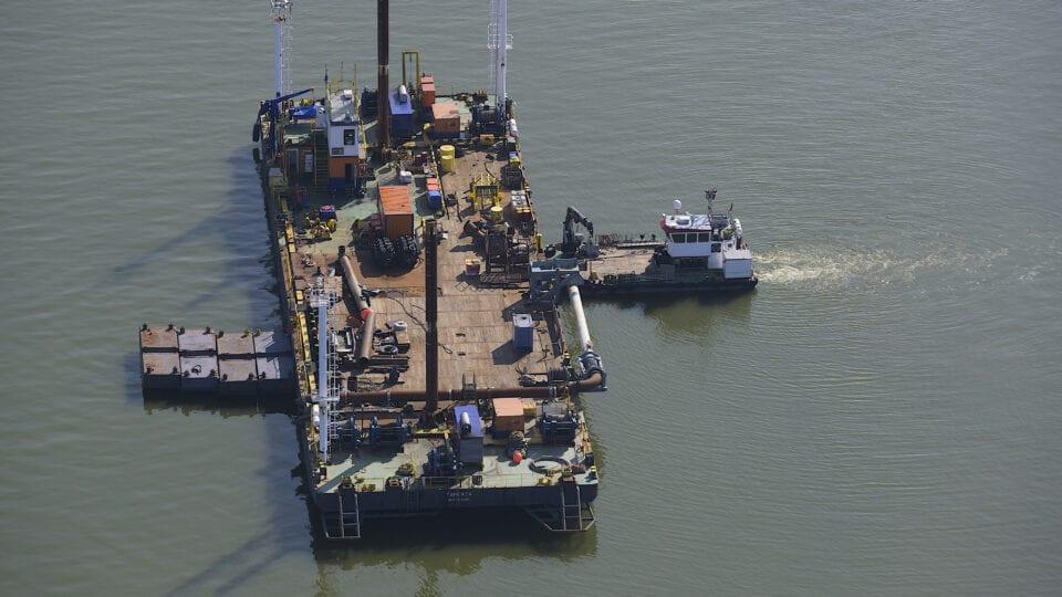 Je ziet een werkschip op het water bij de Afsluitdijk.
