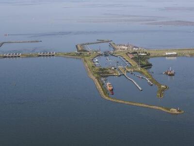 Van boven kijken we uit op de weg en sluizen van de Afsluitdijk.