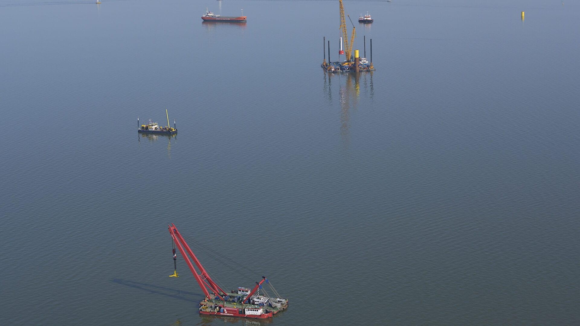 We kijken uit over het water van de Afsluitdijk en er varen verschillende boten met kranen in.