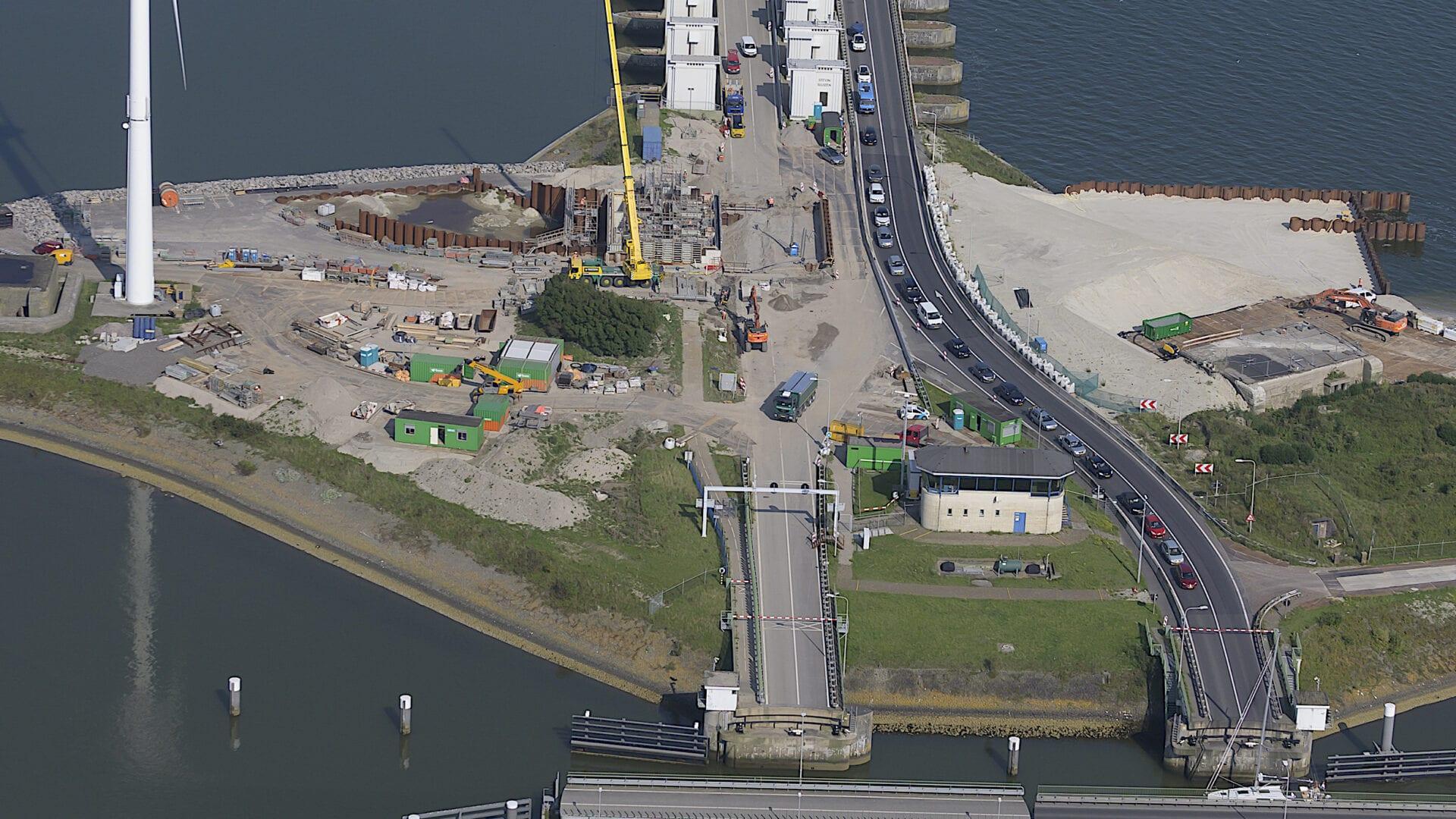 Van boven kijken we uit op de Afsluitdijk. We zien water, de weg en sluizen.